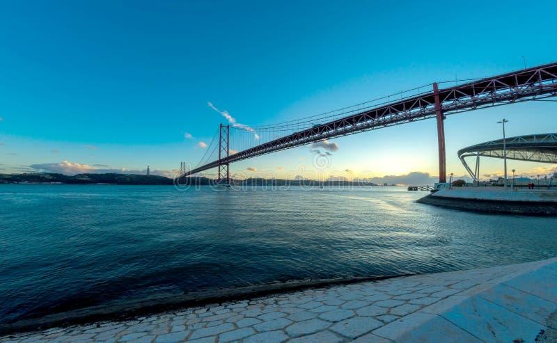 Заход солнца 25th из моста в апреле в Лиссабоне стоковое изображение rf