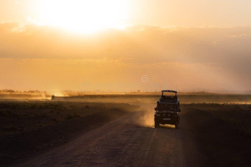 Заход солнца в африканской саванне, силуэтах автомобиля сафари, Африки, Кении, национального парка Amboseli стоковое фото rf