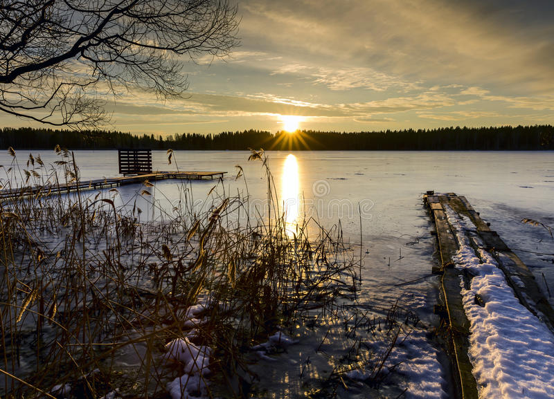 Заход солнца в вечере зимы около замороженного озера стоковые изображения