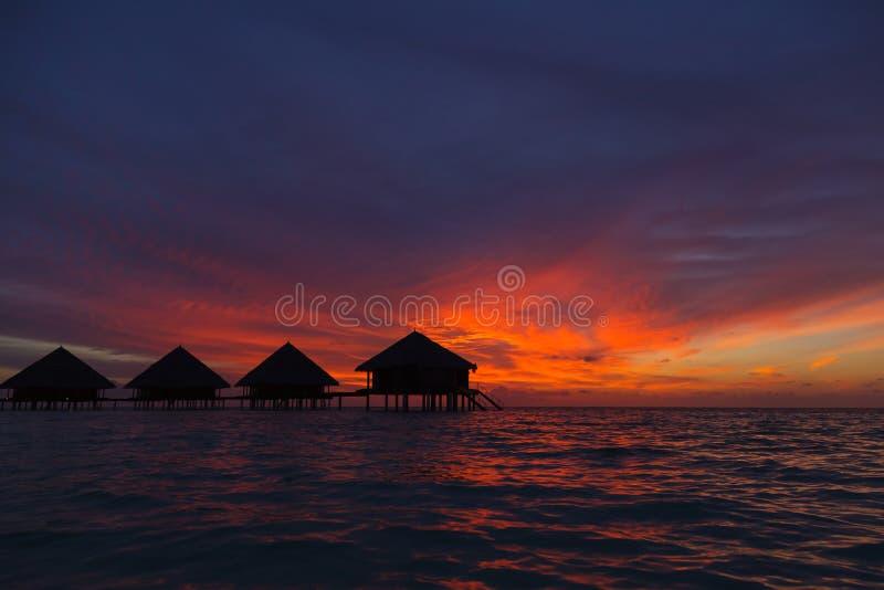 Заход солнца в Мальдивах с целью лагуны и бунгал стоковая фотография