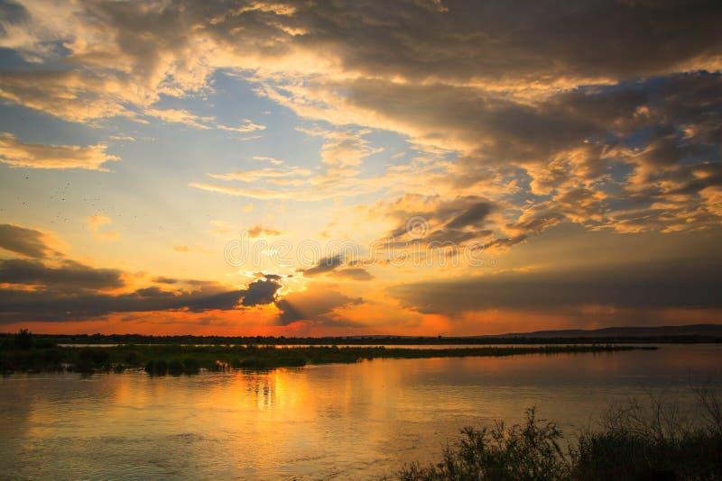 Заход солнца в реке с отражением стоковое фото