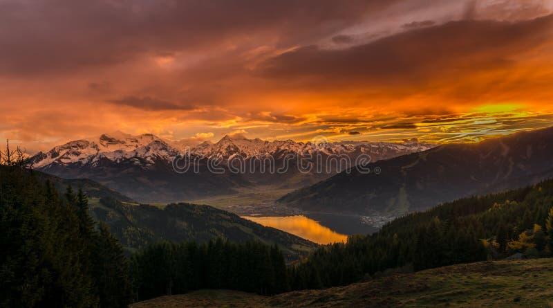 Заход солнца в Zell am видит - Австрию с взглядом к горным вершинам и озеру zeller стоковая фотография