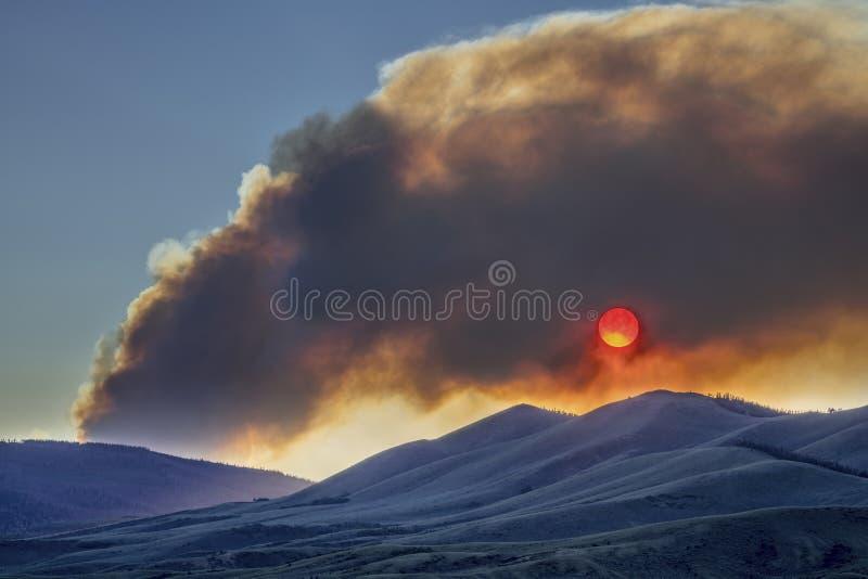 Заход солнца затемненный дымом лесного пожара стоковые фото
