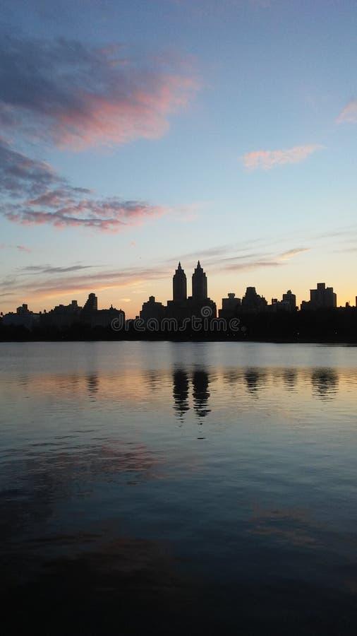 Заход солнца за верхними зданиями западной стороны увиденными от резервуара Жаклина Кеннеди Onassis в Central Park в Манхаттане,  стоковое изображение