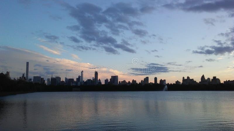 Заход солнца за верхними зданиями западной стороны увиденными от резервуара Жаклина Кеннеди Onassis в Central Park в Манхаттане,  стоковое фото rf