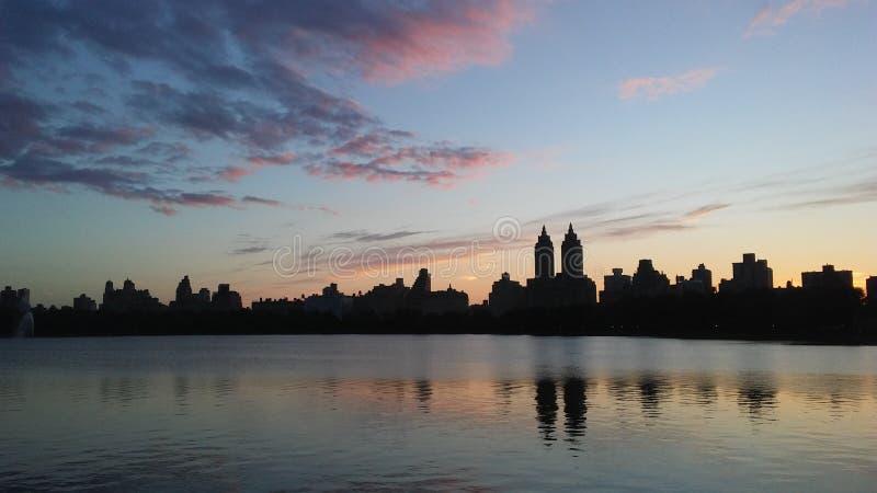 Заход солнца за верхними зданиями западной стороны увиденными от резервуара Жаклина Кеннеди Onassis в Central Park в Манхаттане,  стоковая фотография rf