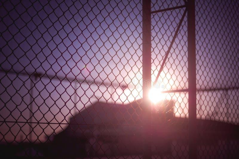 Заход солнца за загородкой стоковые фото