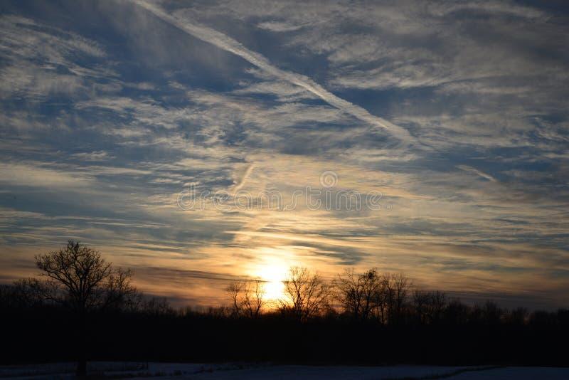 Заход солнца зимы над полем с wispy облаками стоковое изображение rf
