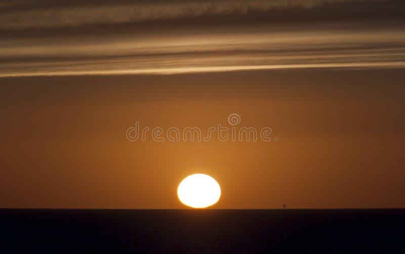 Заход солнца и нефтяная платформа стоковые фото