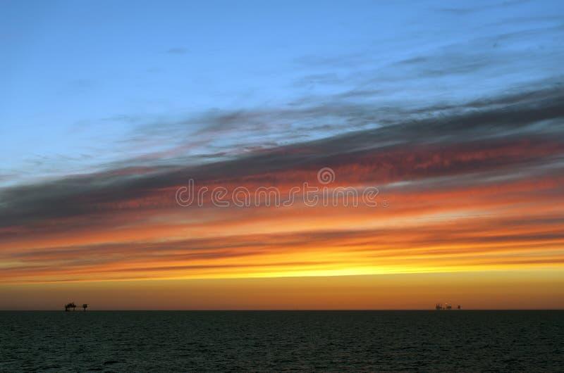 Заход солнца и нефтяная платформа стоковые фотографии rf