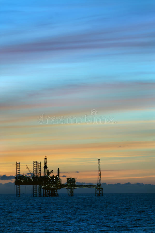 Заход солнца и нефтяная платформа стоковое фото rf