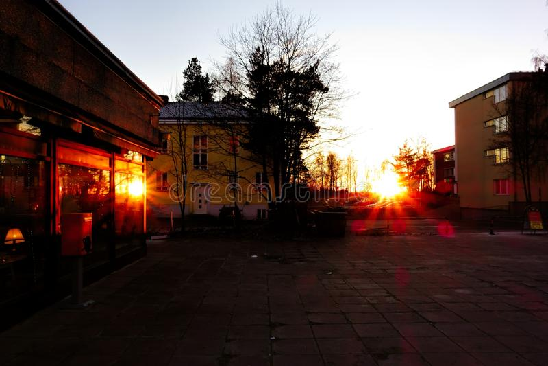 Заход солнца и отражение захода солнца от большого окна создают возникновение глаз солнца в пригородной площади в Хельсинки стоковые изображения