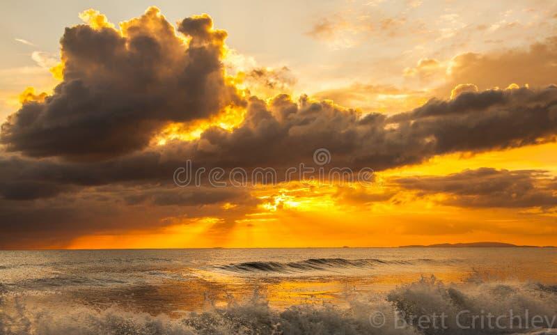 Заход солнца и прибой океана стоковое изображение