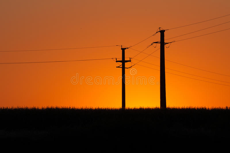 Заход солнца и электрические опоры стоковые фото