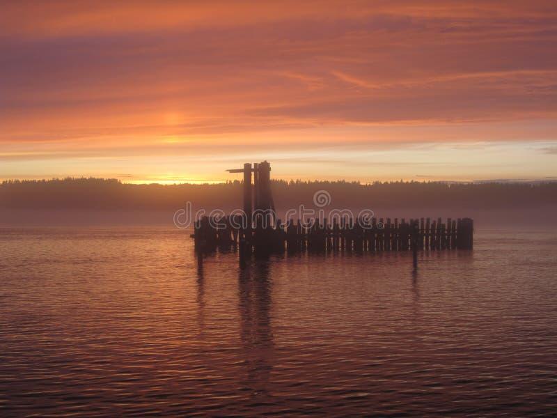 Заход солнца на воде с старой пристанью стоковые фотографии rf