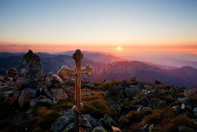 Заход солнца над деревянным крестом стоковое фото