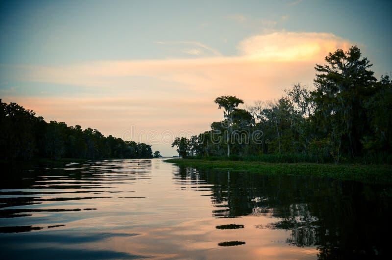 Заход солнца над заболоченным рукавом реки стоковое изображение