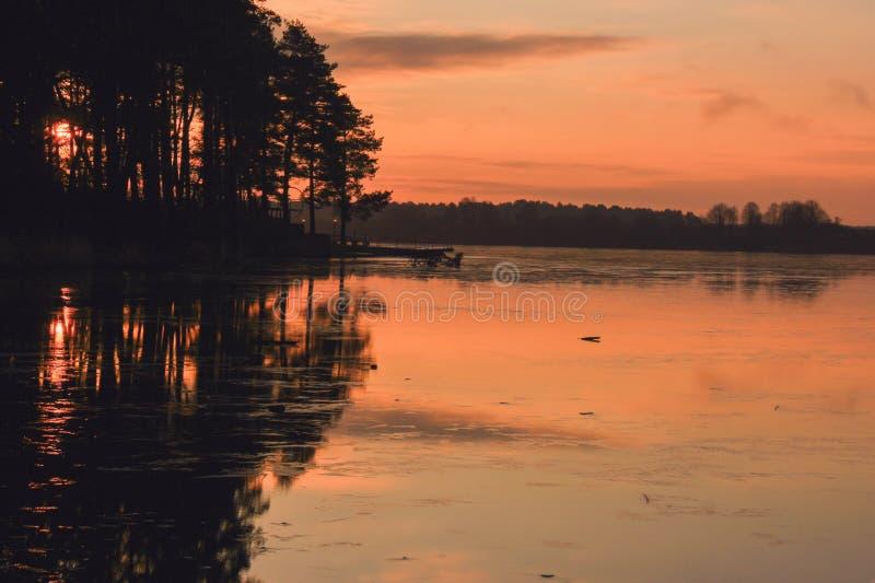 Заход солнца над замерзая озером стоковое изображение