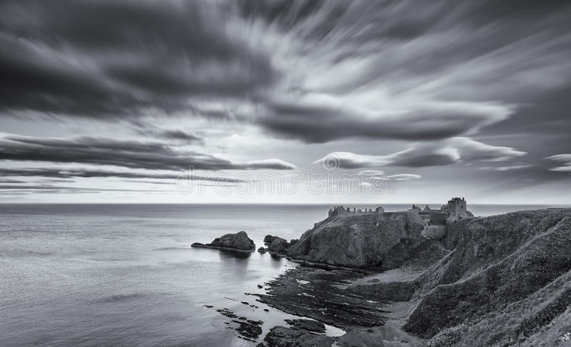Заход солнца на замке Dunnottar на шотландском облаке побережья в черноте стоковые изображения rf