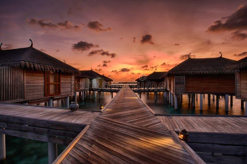 Заход солнца над мальдивскими виллами воды стоковое фото rf