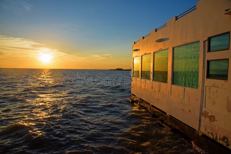 Заход солнца над морем против здания точки зрения стоковые фотографии rf