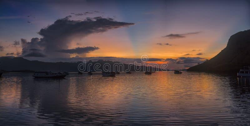 Заход солнца над морем с шлюпкой стоковые изображения