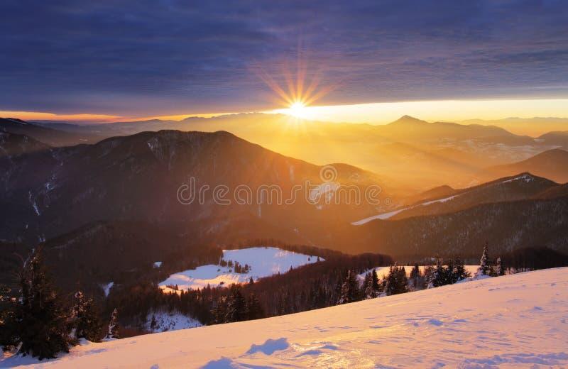 Заход солнца над силуэтом горы цвета с лучами стоковое изображение