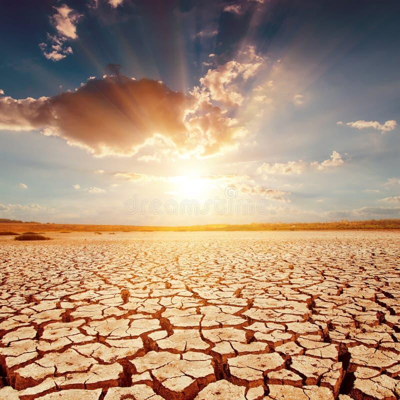 Заход солнца над треснутой землей стоковое изображение rf