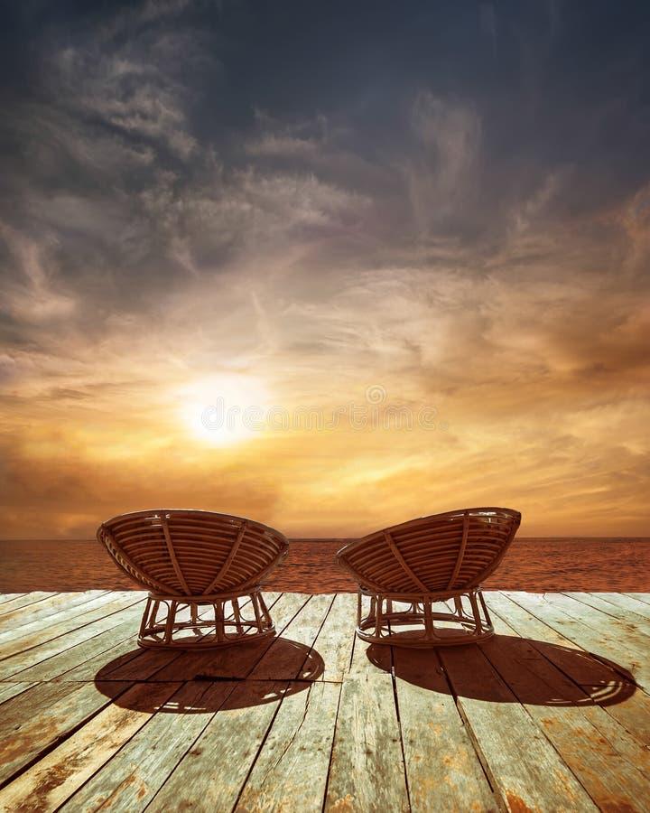 Заход солнца на тропическом пляже океана с стульями для релаксации стоковое изображение