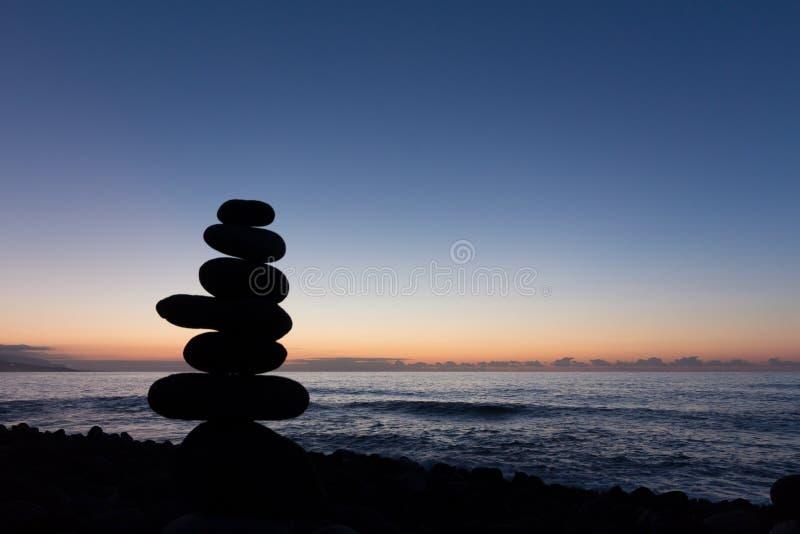 Заход солнца океана с штабелированным каменным силуэтом стоковое фото