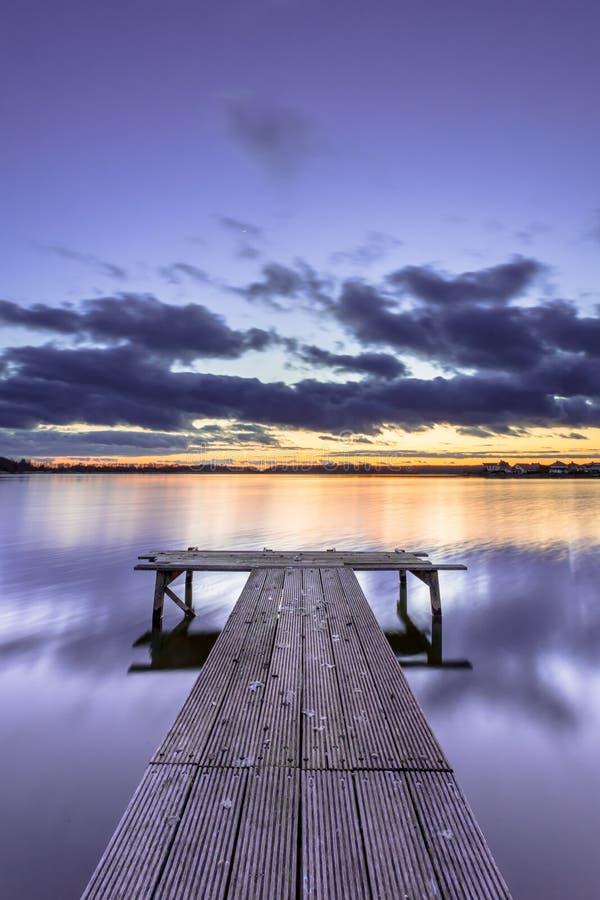 Заход солнца покрашенный пурпуром над спокойным озером с деревянной молой стоковая фотография rf