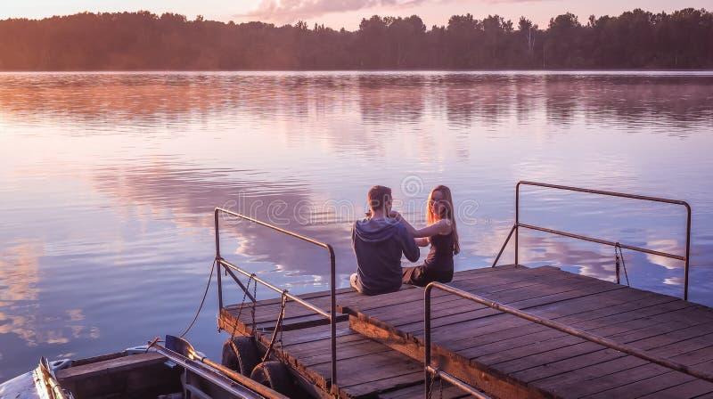 Заход солнца пристани романтичных пар сидя золотой штрихуя собаку Красивое озеро природы заход солнца встречи женщины человека Кр стоковое изображение