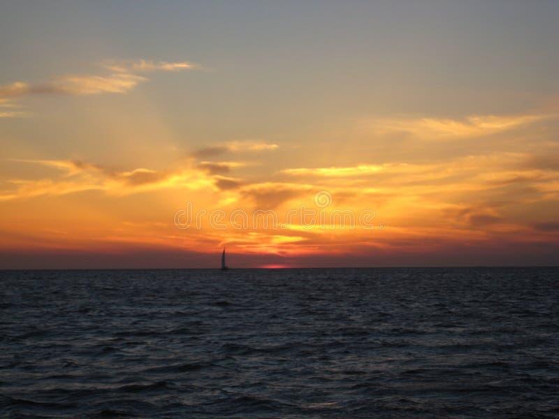 Заход солнца при silhouetted шлюпка стоковые изображения