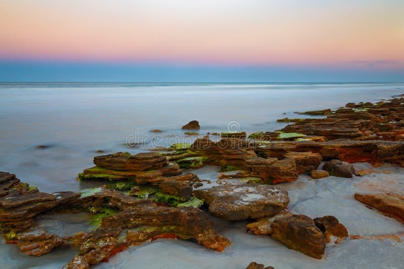Заход солнца скалистого пляжа стоковые изображения