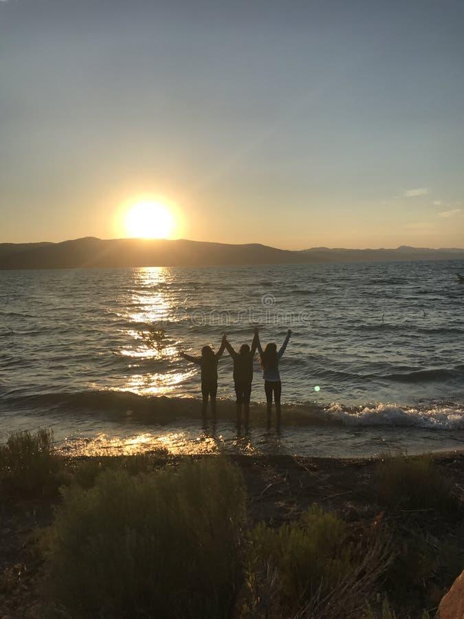 Заход солнца с девушек воды 3 стоковые изображения