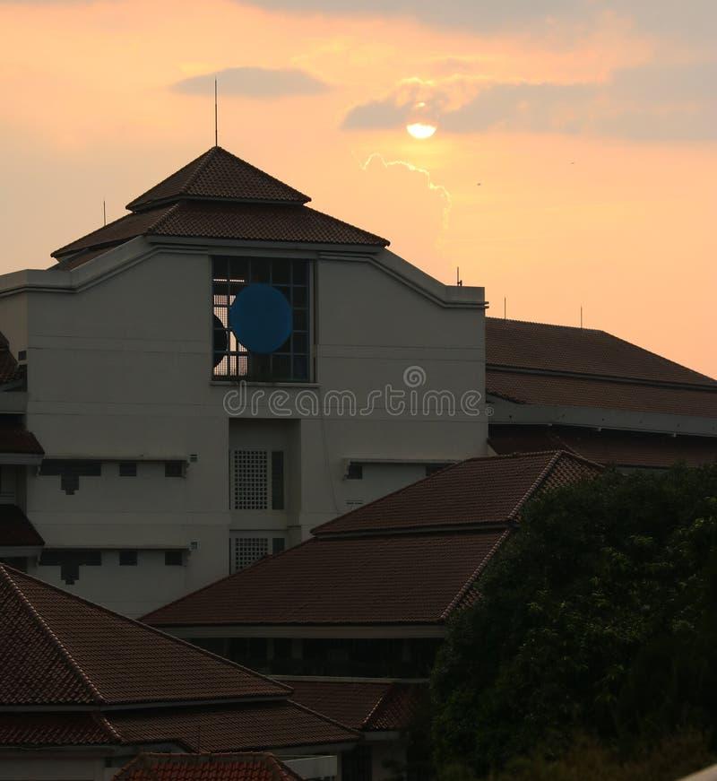 Заходы солнца за зданием стоковое фото