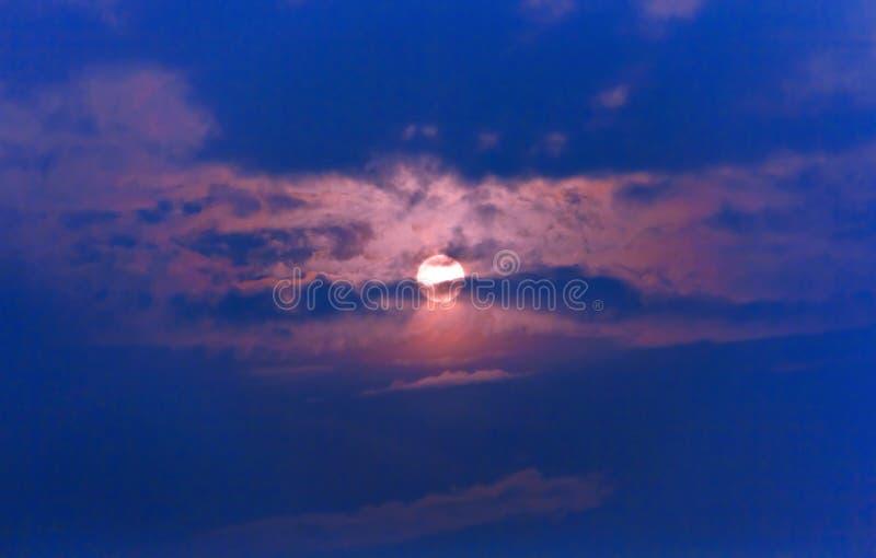 Заходящее солнце на синем небе пряча в облаках стоковая фотография rf