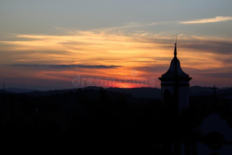 Заходящее солнце с башней церков стоковые фотографии rf