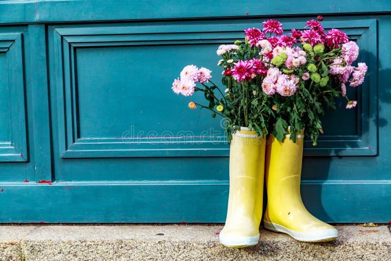 зацветите букет представленный на пластичных ботинках перед дверью стоковое изображение