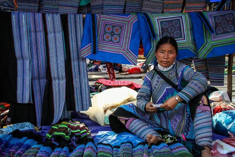 Зацветите женщина hmong продавая традиционные ткани на рынке Bac Ha, Lao Cai, Вьетнаме стоковые изображения