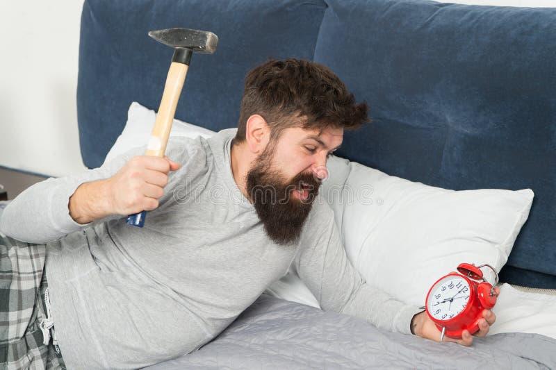 Зацепляйте вверх пропущенный сон во время выходных r Несчастное человека бодрствующее со звенеть будильника Хотя вы стоковое изображение rf
