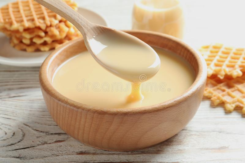 Зачерпните ложкой лить сконденсированное молоко над шаром на таблице, крупном плане стоковая фотография