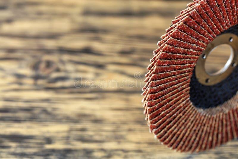 Зашкурить диск для древесины и металла на предпосылке старой деревянной доски в нерезкости стоковые фото