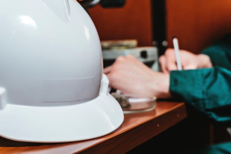Защитные руки шлема пишут что-то стоковые фото