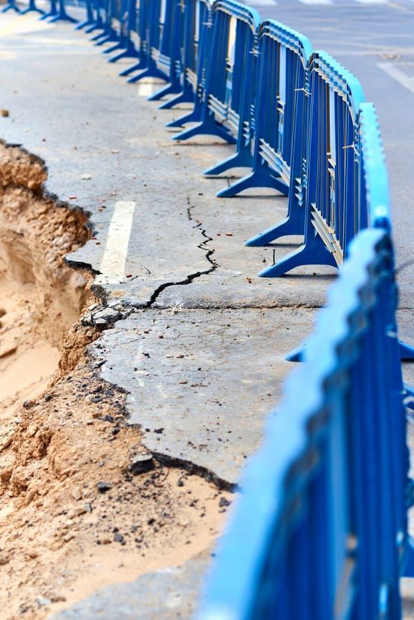 Защитный барьер и разрушенная дорога асфальта стоковое фото