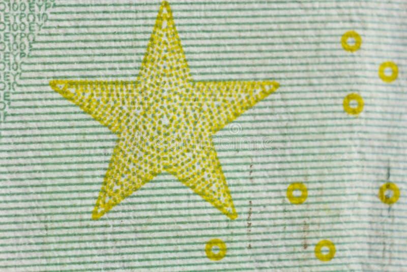 Защитный водяной знак на 100 счетах евро в макросе защита против подделывать банкнот hologram деталь бумаги стоковое изображение