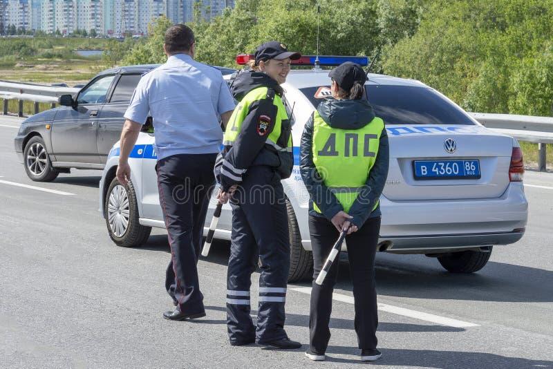 Защищено полицейский и девушки 2 офицера около патрульной машины в городе с общественным движением r стоковое изображение rf