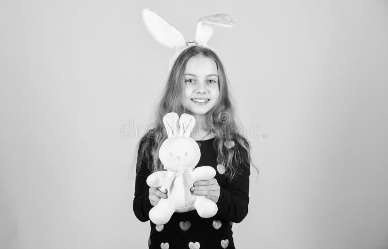 Заяц символ рождаемости и весны Небольшой ребенк получая белый подарок зайцев на день пасхи Маленькая девочка держа пасху стоковые изображения rf