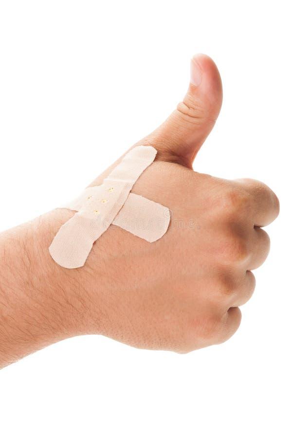 Залатанная рука показывая ОДОБРЕННЫЙ знак стоковое изображение