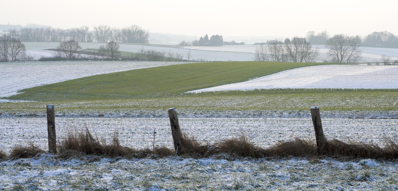 за загородкой fields неровная зима стоковое изображение